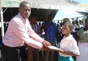 Kinango officer of registration of Persons  - Lenard Maluvu - handing over birth certificate to a student